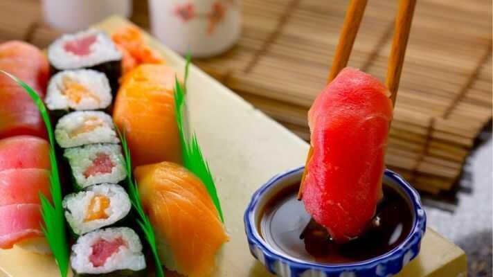 寿司を醤油につけている